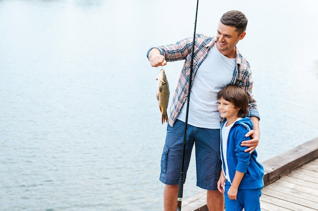 Look what we caught! father holding fishing rod and showing big fish to his son