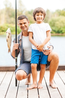 Look what we caught! father and son looking at camera and smiling while man holding fishing rod with big fish on the hook