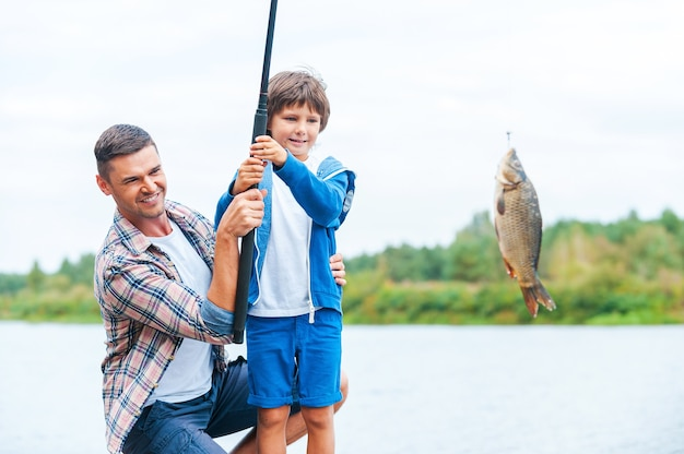 Look what we caught! father and son stretching a fishing rod with fish on the hook