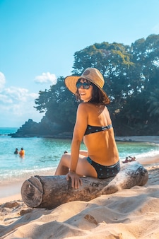 Look of a young woman with a hat sitting on a log on the beach of punta sal in tela