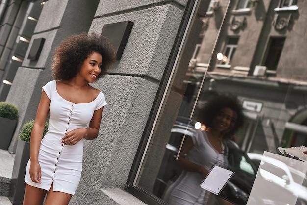 笑顔と探しているセクシーな白いドレスで驚くほど魅力的で陽気なアフロアメリカ人女性を探しています
