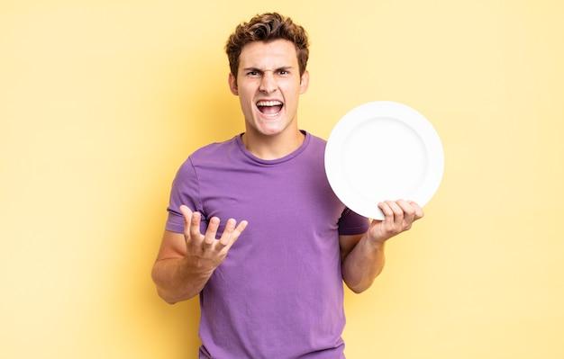Looking angry, annoyed and frustrated screaming wtf or whatãƒâƒã'â¢ãƒâ'ã'â€ãƒâ'ã'â™s wrong with you. empty plate concept