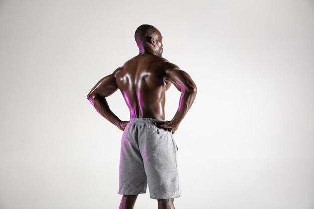 Alla ricerca di risposte. studio shot di giovani afro-americani formazione culturista su sfondo grigio. singolo modello maschio muscoloso in piedi in abbigliamento sportivo. concetto di sport, bodybuilding, stile di vita sano.