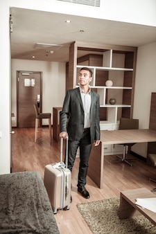 Looking around. dark-haired young prosperous businessman looking around the hotel room