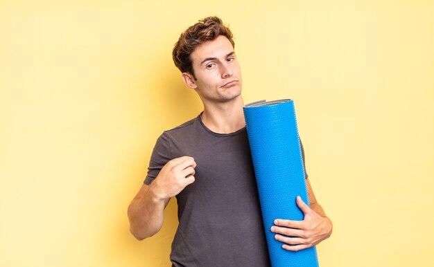 Выглядит высокомерным, успешным, позитивным и гордым, указывая на себя. концепция коврика для йоги