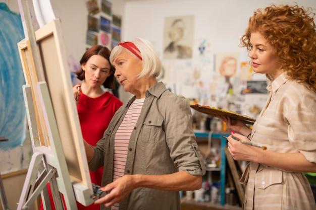 アーティストを見てください。キャンバスに絵を描く有名な芸術家を見ている2人の若い才能のある女性