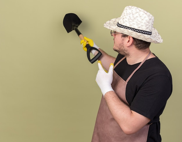 ガーデニング帽子と手袋を着た若い男性庭師の後ろにスペードを付けて、コピースペースのあるオリーブグリーンの壁に隔離されている