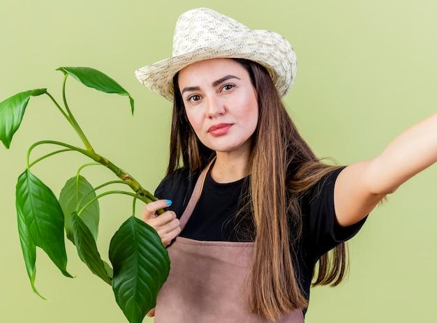 カメラを見て、オリーブグリーンの背景に分離された植物とカメラを保持している園芸帽子を身に着けている制服を着た美しい庭師の女の子