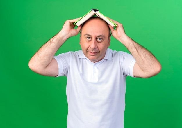녹색 배경에 고립 책으로 카메라 캐주얼 성숙한 남자 덮여 머리를 찾고