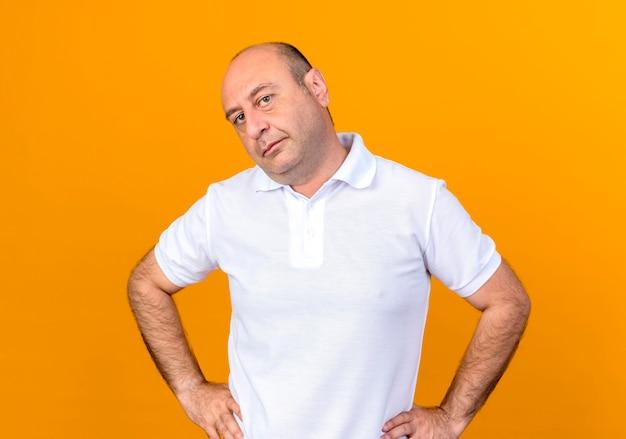黄色の背景に分離された腰に手を置くカメラカジュアル成熟した男を見て