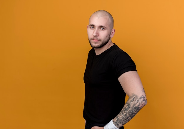 コピースペースでオレンジ色の背景に分離された腰に手を置くリストバンドを身に着けているカメラに自信を持って若いスポーティな男を見て