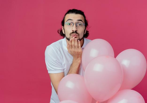 風船を保持し、ピンクの背景に分離されたキスジェスチャーを示す眼鏡をかけているカメラのハンサムな男を見て