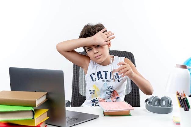 Глядя на камеру, маленький школьник сидит за столом со школьными инструментами, держа стакан воды и прикрытый лоб запястьем, изолированным на белом фоне