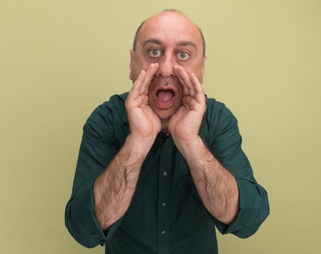 緑の t シャツを着た中年男性が、オリーブ グリーンの壁に隔離された誰かに電話をかけるカメラを見ている