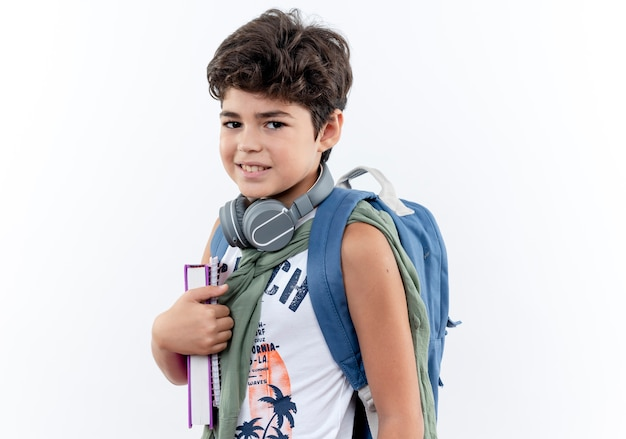 カメラを見て喜んでバックバッグと白い背景で隔離の本を保持しているヘッドフォンを身に着けている小さな男子生徒