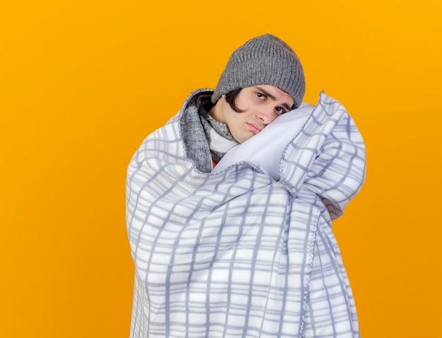 오렌지에 고립 된 격자 무늬에 싸여 스카프와 겨울 모자를 쓰고 카메라 슬픈 젊은 아픈 남자를 찾고