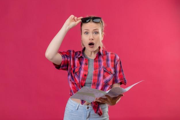 孤立したピンクの壁に地図を保持している彼女の頭に赤いシャツと眼鏡を身に着けているカメラを見て驚いた若い女性旅行者