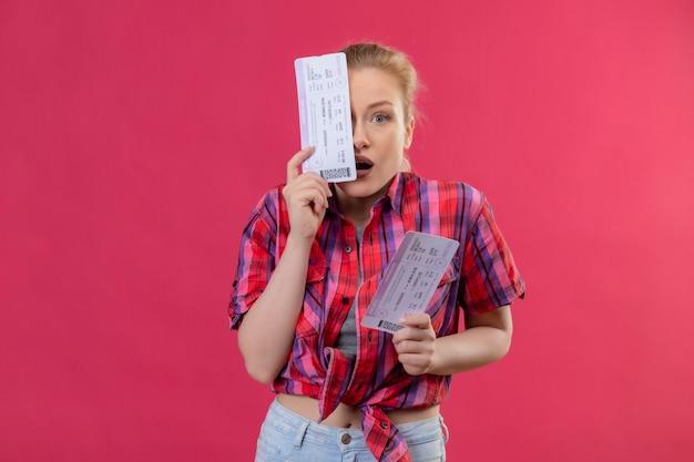 Глядя в камеру, удивленная молодая женщина-путешественница в красной рубашке закрыла глаза билетом на изолированной розовой стене