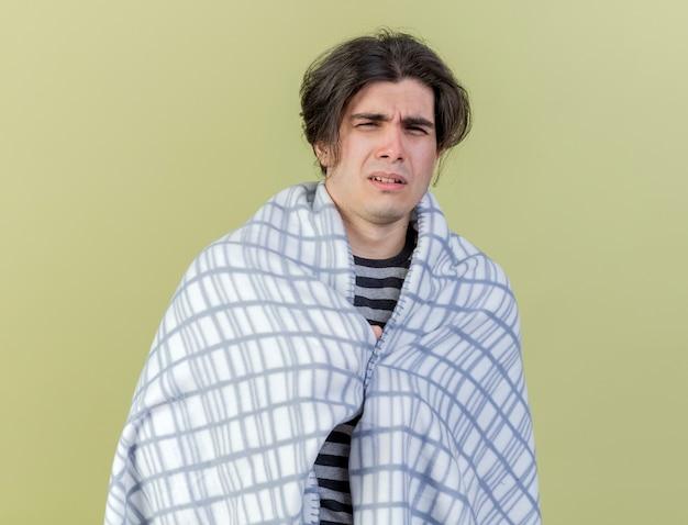 올리브 그린에 고립 된 격자 무늬에 싸여 카메라 불쾌한 젊은 아픈 남자를보고