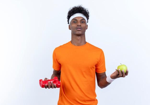 カメラを見て白い背景で隔離のリンゴとダンベルを保持しているヘッドバンドとリストバンドを身に着けている若いアフリカ系アメリカ人のスポーティな男