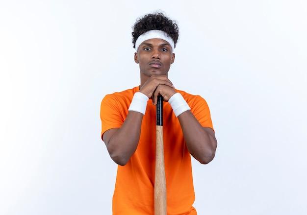 Глядя на камеру, молодой афро-американский спортивный мужчина с повязкой на голову и браслет, положив подбородок на летучую мышь, изолированную на белом фоне