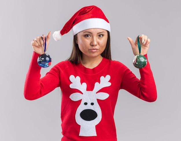 흰색 배경에 고립 된 크리스마스 트리 볼을 들고 스웨터와 크리스마스 모자를 쓰고 카메라 젊은 아시아 여자를 찾고