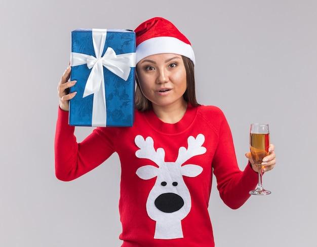 Глядя на камеру, молодая азиатская девушка в новогодней шапке со свитером держит подарочную коробку с бокалом шампанского, изолированную на белом фоне