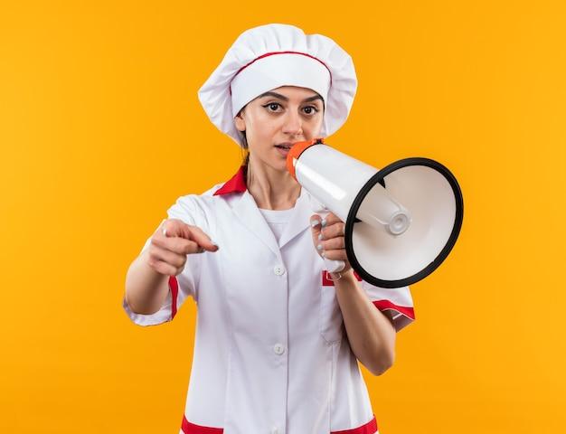카메라를 보고 요리사 유니폼을 입은 아름다운 소녀가 당신에게 제스처를 보여주는 확성기에서 말합니다