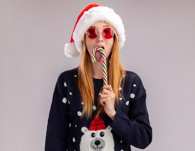 白い背景で隔離のクリスマスのキャンディーを保持し、なめるクリスマスの帽子と眼鏡を身に着けているカメラの若い美しい少女を見て