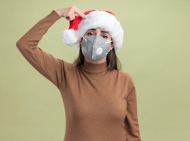 올리브 녹색 배경에 고립 된 권총 제스처와 함께 자살을 보여주는 의료 마스크와 크리스마스 모자를 쓰고 카메라 젊은 아름 다운 소녀를 찾고