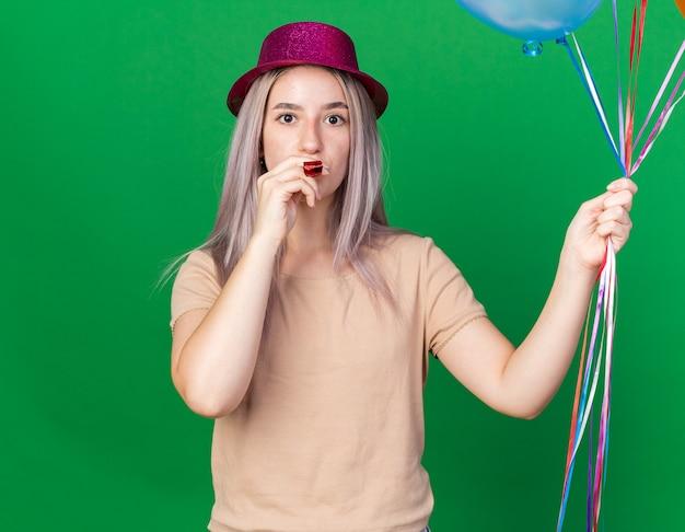 カメラを見てパーティーハットを身に着けている若い美少女が口の中でパーティーホイッスルを保持