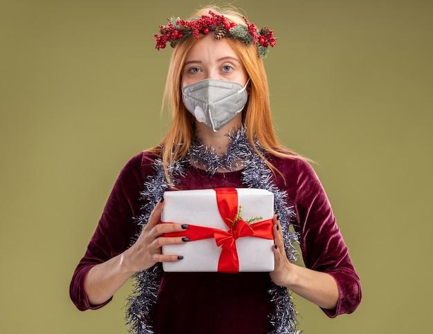 オリーブグリーンの背景で隔離のギフトボックスを保持している首に花輪と花輪の赤いドレスと医療マスクを身に着けているカメラを見て若い