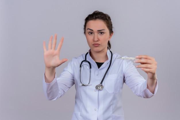 温度計を保持している聴診器を身に着けている医療用ガウンを身に着けているカメラの若い医者を見て、白い壁に停止ジェスチャーを示しています