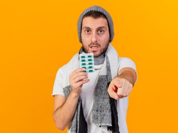 겨울 모자와 스카프를 착용하고 약을 들고 노란색에 고립 된 제스처를 보여주는 카메라 젊은 아픈 남자를보고