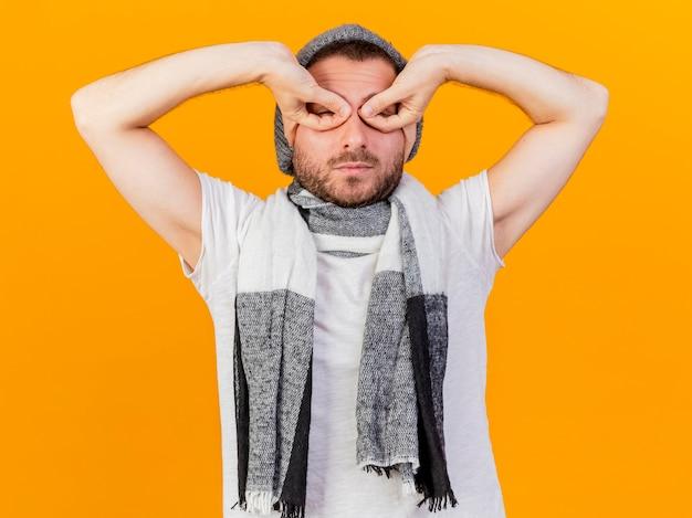 노란색 배경에 고립 손으로 겨울 모자와 스카프 만들기 마스크를 쓰고 카메라 젊은 아픈 남자를 찾고