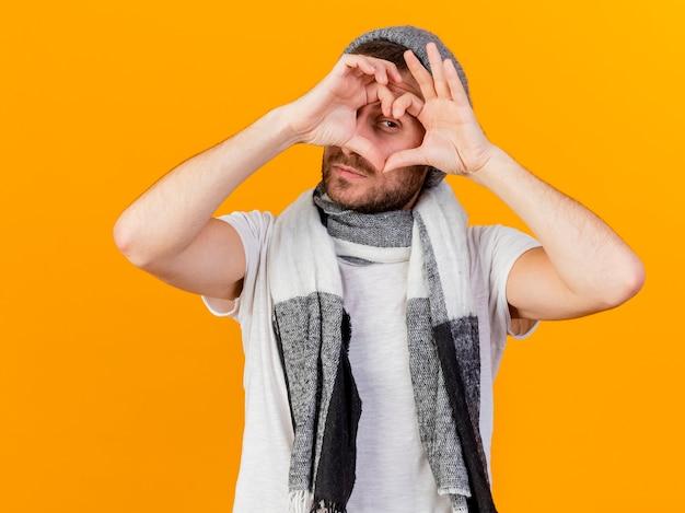 노란색 배경에 고립 된 심장 제스처를 보여주는 겨울 모자와 스카프를 착용 카메라 젊은 아픈 남자를 찾고