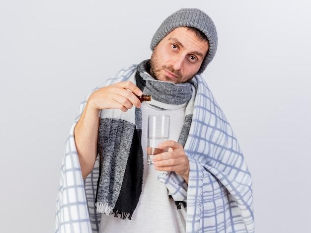 약을 붓는 격자 무늬에 싸여 겨울 모자와 스카프를 착용 카메라 젊은 아픈 남자를 찾고