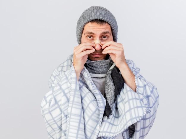 흰색에 고립 된 코에 석고를 넣어 격자 무늬에 싸여 겨울 모자와 스카프를 착용 카메라 젊은 아픈 남자를 찾고