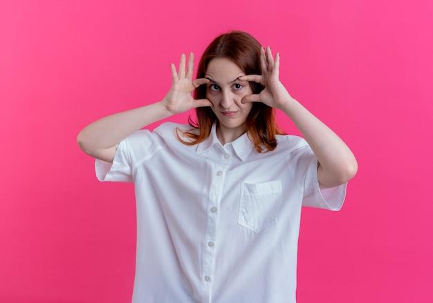분홍색 배경에 고립 손으로 눈을 뜨고 카메라 젊은 빨간 머리 소녀를보고