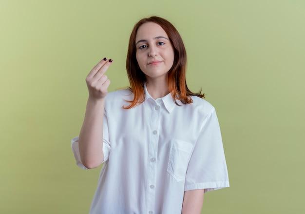 올리브 녹색 배경에 고립 팁 제스처를 보여주는 카메라 젊은 빨간 머리 소녀를 찾고 무료 사진
