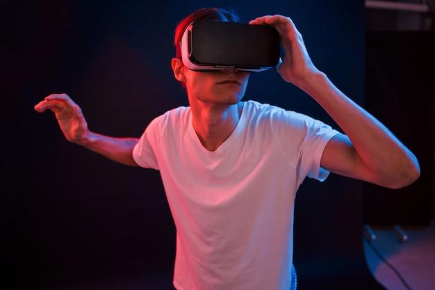 Смотрим на детали. молодой человек в очках виртуальной реальности в темной комнате с неоновым освещением