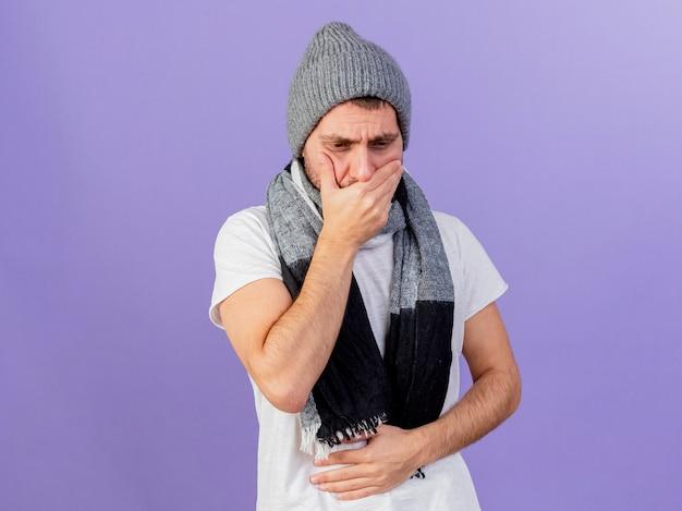 스카프는 mout에 손을 잡고 보라색 배경에 고립 된 아픈 배를 잡고 겨울 모자를 쓰고 젊은 아픈 남자를 내려다보고