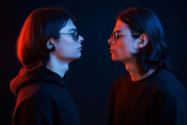 Смотрим друг на друга. креативное фото. портрет братьев-близнецов. студия снята в темной студии с неоновым светом.