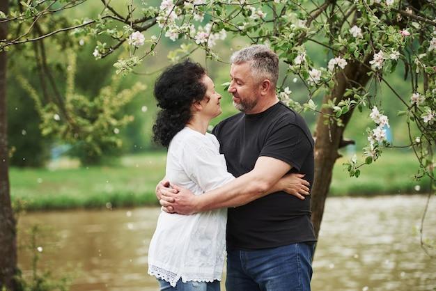 愛を込めてお互いを見つめる。屋外で素敵な週末を楽しんでいる陽気なカップル。良い春の天気