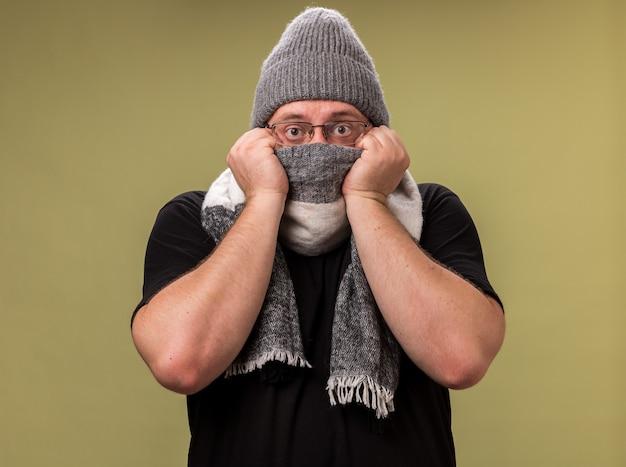冬の帽子とスカーフを身に着けている正面の中年の病気の男性を見てオリーブグリーンの壁に分離されたスカーフで顔を覆った