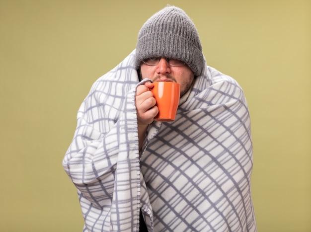 オリーブグリーンの壁に隔離されたカップから格子縞の飲み物のお茶に包まれた冬の帽子とスカーフを身に着けている正面の中年の病気の男性を見て