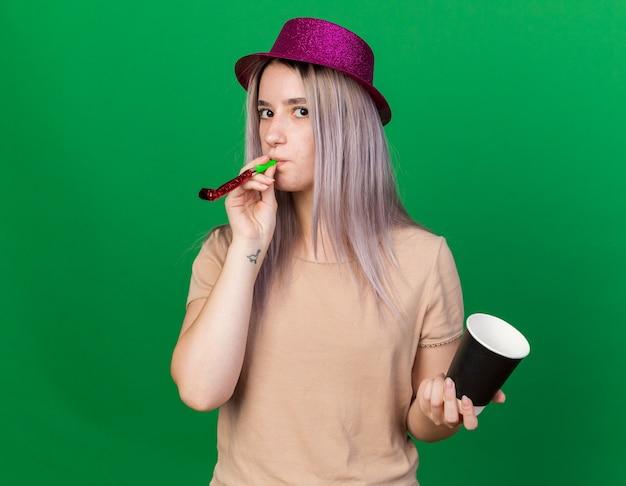 緑の壁に隔離されたコーヒーのカップを保持しているパーティーの笛を吹くパーティー帽子をかぶって正面の若い美しい女性を見て