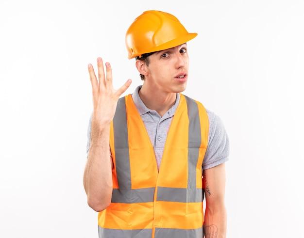흰 벽에 격리된 4개를 보여주는 제복을 입은 앞의 젊은 건축업자 남자를 보고