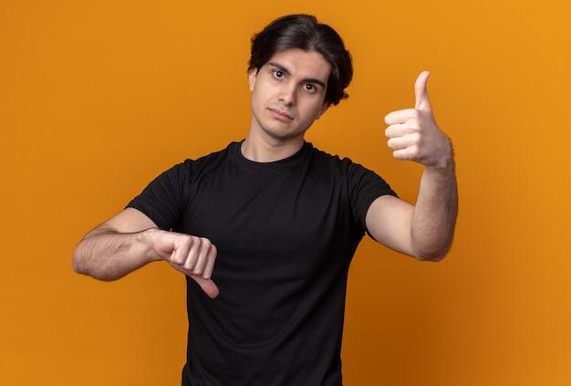 オレンジ色の壁に分離された親指を上下に示す黒いtシャツを着ている正面の若いハンサムな男を見て