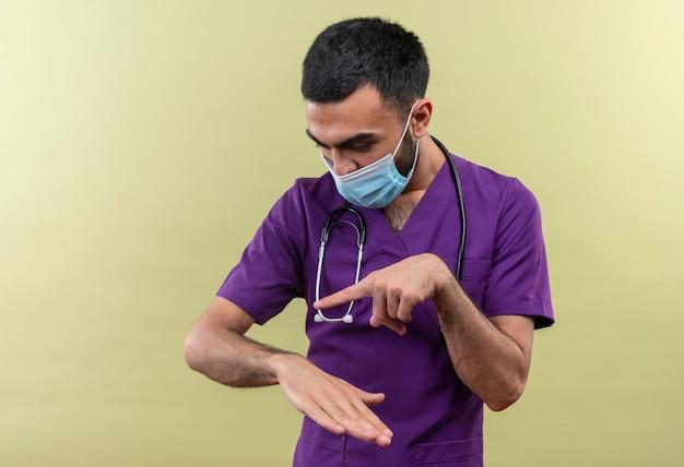 孤立した緑の壁に手首の時計のジェスチャーを示す紫色の外科医の服と聴診器の医療マスクを身に着けている若い男性医師を見て